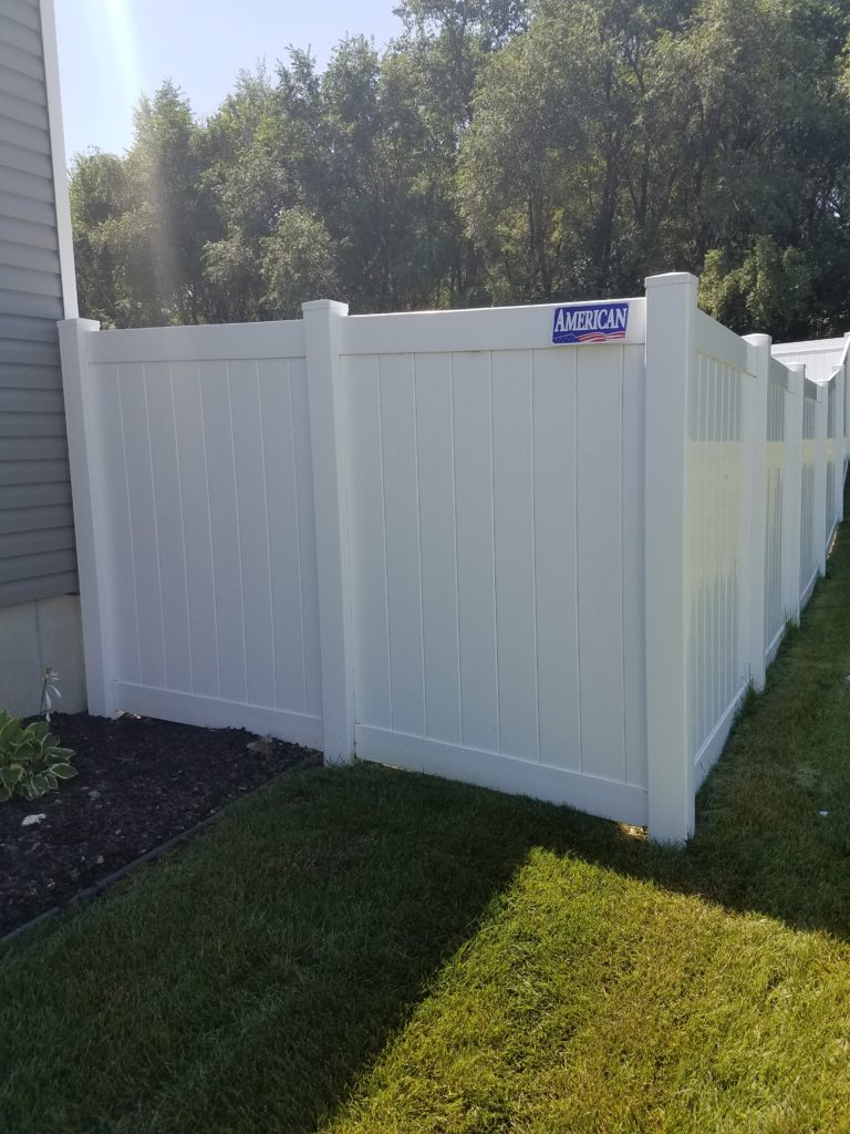 6' tall white solid vinyl fence with the American Fence Company name plate